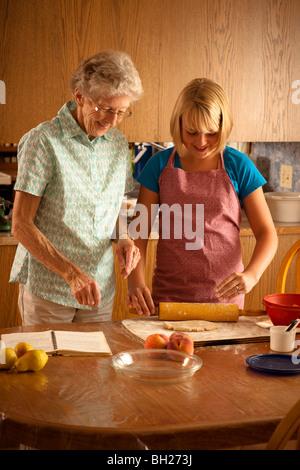 Hauts femme et son arrière petite-fille de douze ans cuisson; Redvers, Saskatchewan, Canada Banque D'Images