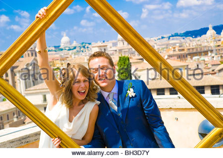 Portrait of young Bride and Groom holding photo frame Banque D'Images
