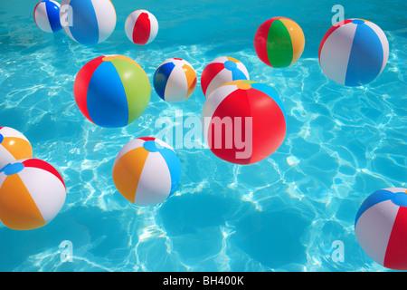 Des ballons de plage gonflables flottant au hasard dans une piscine d'eau bleue Banque D'Images