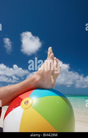 Une jambes et pieds reposant sur une structure gonflable ballon de plage multicolores sur une plage tropicale Banque D'Images