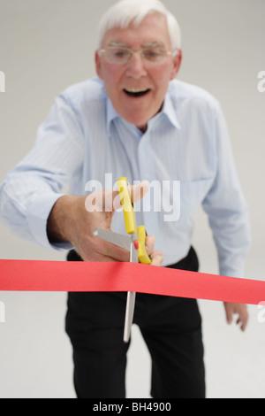 Senior businessman à propos de couper à travers une bande rouge, rire Banque D'Images