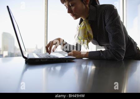 Une femme d'affaires à l'aide d'un ordinateur portable sur un bureau bureau avec une expression grave Banque D'Images