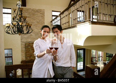 Les jeunes Chinois couple drinking wine at home Banque D'Images