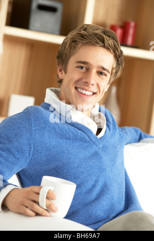 Jeune homme se détendre avec une tasse de café Banque D'Images