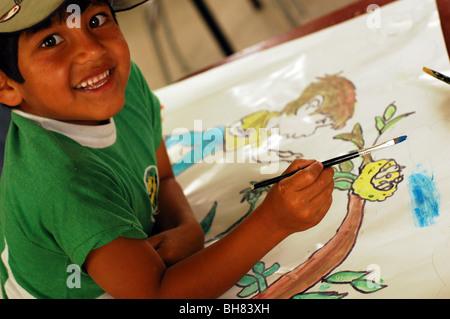 L'Équateur, Yuarmachoa, vue latérale d'une peinture d'un garçon garçon debout par un arbre avec un nid et un oiseau Banque D'Images