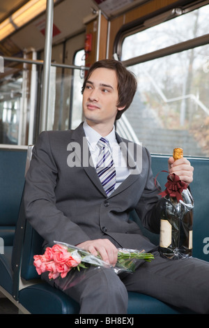 Businessman in tube, champagne, fleurs Banque D'Images