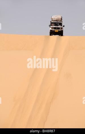 Un désert safari Land cruiser 4x4 Jeep écussons une dune de sable géant dans la grande mer de sable du désert occidental, Banque D'Images