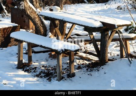 Des bancs et table sous la neige dans le jardin d'hiver Banque D'Images