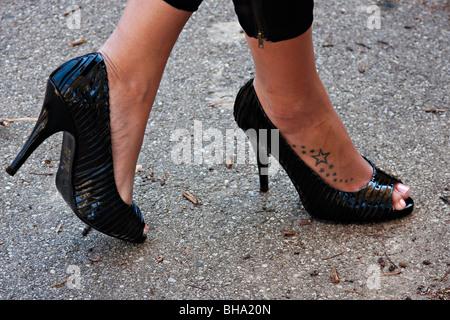 Close up sur les jambes croisées dans un sombre à haut talon chaussures; montrant tatouage sur la jambe Banque D'Images