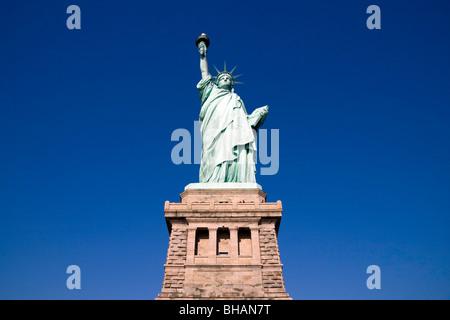 La Statue de la liberté face à l'encontre d'un ciel bleu clair sur une journée ensoleillée avec le socle visible Banque D'Images