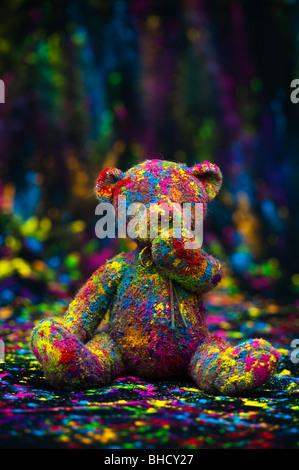 Ours assis sur un tissu noir recouvert de poudre de couleur. Still Life Banque D'Images