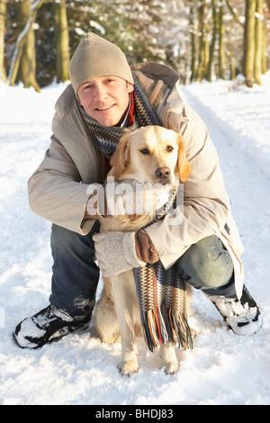 Homme marchant chien au bois enneigé Banque D'Images