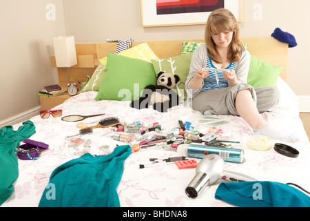 Teenage Girl dans une chambre en désordre l'épilation des jambes Banque D'Images