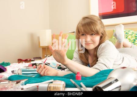 Teenage Girl dans une chambre mal rangée de clous de peinture Banque D'Images