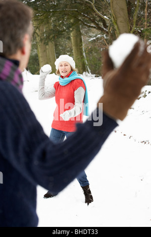 Senior Couple Having Snowball Fight In Snowy Woodland Banque D'Images