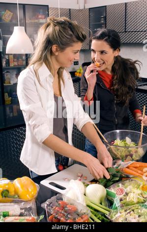 Deux jeunes femmes dans la cuisine, préparer le dîner ensemble Banque D'Images