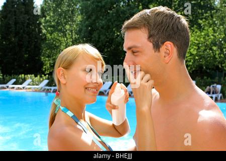Appliquez un écran solaire femme à l'homme son nez au bord de la piscine Banque D'Images