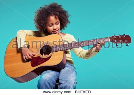 Girl playing acoustic guitar Banque D'Images