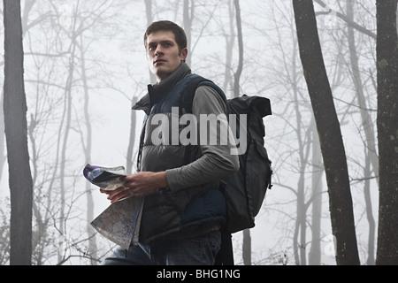 Un jeune male hiker holding une carte dans une forêt brumeuse Banque D'Images