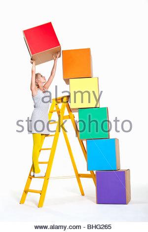 Woman stacking boîtes colorées Banque D'Images