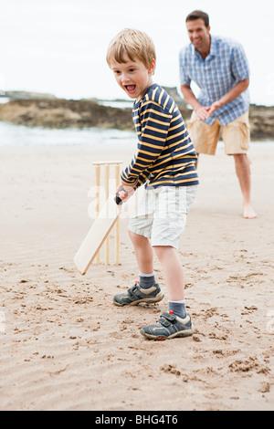 Père et fils à jouer au cricket sur la plage