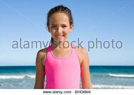 Portrait de petite fille à la plage en maillot rose vif Banque D'Images