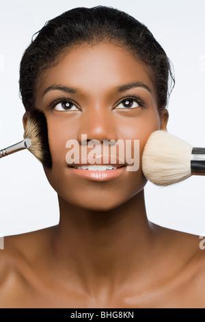 Femme avec des brosses de maquillage sur le visage Banque D'Images