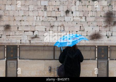 Femme avec parapluie à la recherche au mur occidental à Jérusalem, vieille ville Banque D'Images
