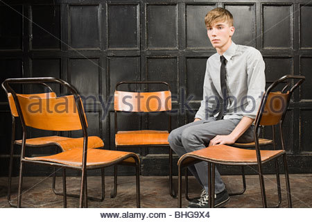 Teenage boy sitting on chair Banque D'Images