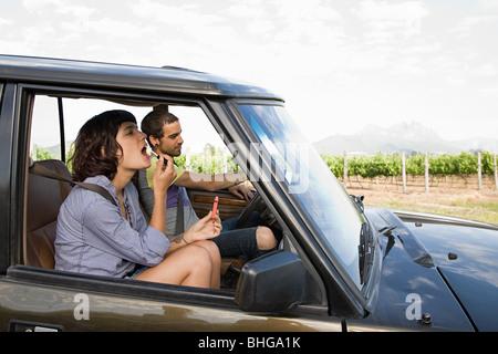 Woman putting on lipstick en véhicule Banque D'Images