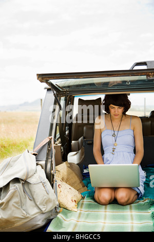 Young woman using laptop in dos de suv Banque D'Images