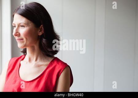 Femme en robe rouge standing at window