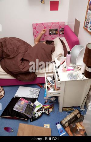 Une jeune fille endormie dans son chambre malpropre Banque D'Images