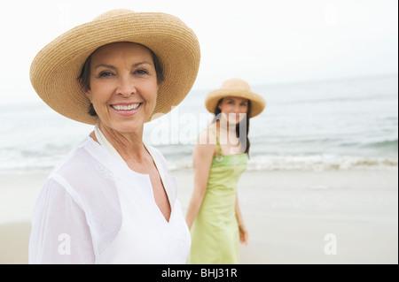 Mère et fille dans sunhats on beach Banque D'Images