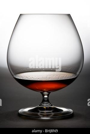Verre à cognac contre de blanc à l'obscurité. Cognac gouttes couler sur des murs en verre. Banque D'Images