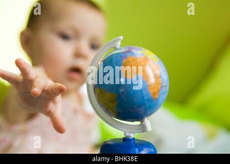 La fille d'atteindre pour le jouet globe Banque D'Images