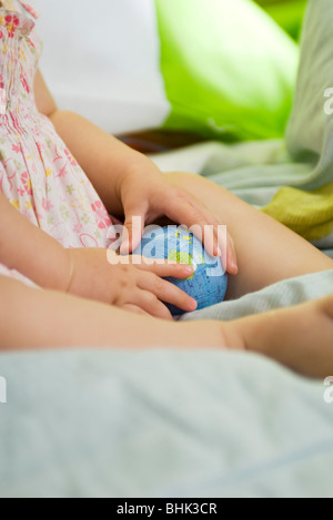 Infant holding toy globe, cropped Banque D'Images