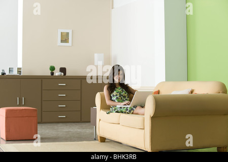 Teenage girl relaxing on sofa using laptop in living room Banque D'Images