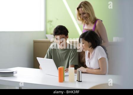 L'observation d'mère fils adolescent et sa fille à l'aide d'un ordinateur portable Banque D'Images
