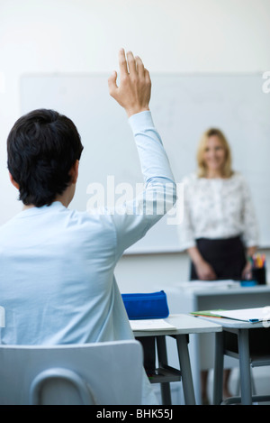 High school student raising hand in class