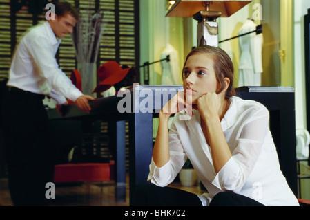 Jeune femme assise avec les mains sous le menton en magasin de vêtements, l'homme à l'aide du tableau en arrière Banque D'Images