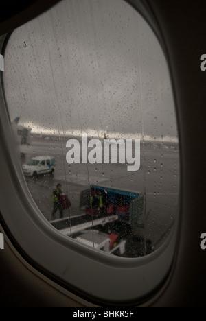 Les préposés aux bagages Bagages charge sur un avion du passager sous la pluie. Banque D'Images