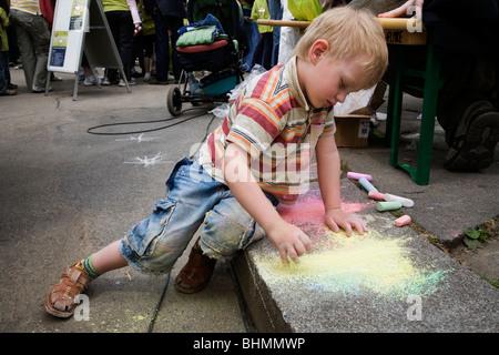 Jeune garçon avec dessin et peinture craie de couleur dans la chaussée, Dresden, Allemagne Banque D'Images