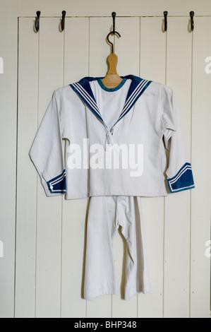 Costume de Marin enfant accroché sur la porte en bois blanc Banque D'Images