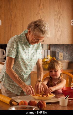 Hauts Femme et fille de cinq ans de placer les pêches dans l'assiette à tarte; Redvers, Saskatchewan, Canada Banque D'Images