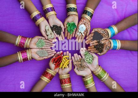 Enfants indiens mains tenant divers cuisine indienne épices contre un fond violet. L'Inde Banque D'Images