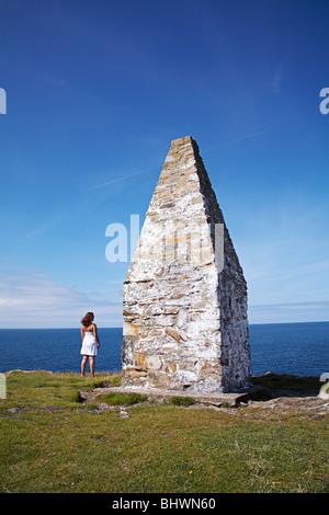 Femme se tenait face à la mer à côté de la balise à Porthgain côtières, le long sentier côtier du Pembrokeshire Banque D'Images