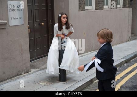 Jeune fille en premier auteur de la robe blanche sur le bollard vu par boy en noir devant notre Dame du Mont Carmel Banque D'Images