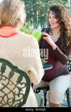 Femme enceinte avec cadeau de l'ami à la table d'Extérieur, Manitoba, Canada Banque D'Images