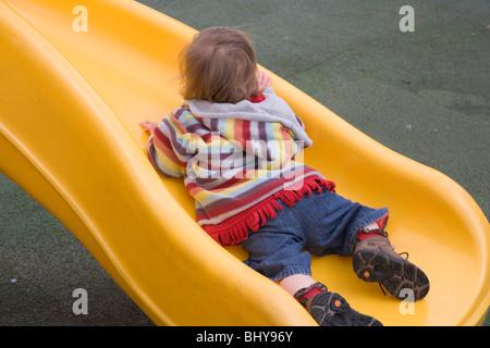 16 mois bébé fille est couchée sur le toboggan en plastique jaune Banque D'Images